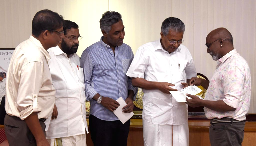 Kochi Biennale Foundation president, Bose Krishnamachari hands over an amount of Rs 3-crore  to Kerala CM Pinarayi Vijayan towards the Chief Minister's Distress Relief Fund for the 2018 flood victims, at the CMO, Thiruvananthapuram on July 10. From l - Kadakampally Surendran