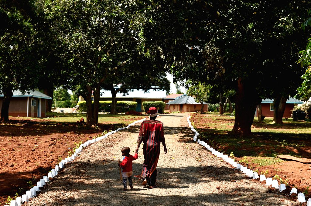 A mother and her child walk on a road at Kogelo Village in Siaya, Kenya, June 29, 2015. Barack Obama, current President of the United States, has made several trips ...