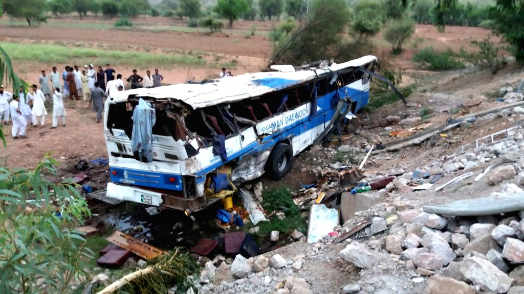 KOHAT (PAKISTAN), Aug. 4, 2018 People gather near a damaged passenger bus on the site of an accident in Pakistan's northwestern district of Kohat, on Aug. 4, 2018. At least 14 people were ...