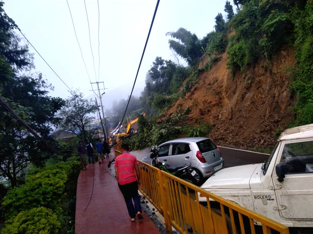 Kohima: An earth mover clears the mud lying on a road between SKV Petrol Pump and Mezhur Higher Secondary School that was blocked in a landslide, in Nagaland's Kohima on Aug 4, 2019. (Photo: IANS)