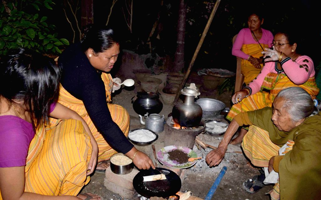 Women prepare traditional delicacies ahead of Bhogali Bihu in Kokrajhar of Assam on Jan 11, 2015.