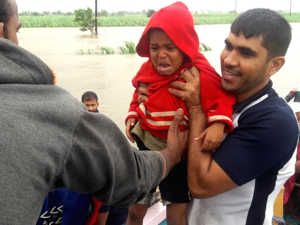 Kolhapur: A child being rescued in Maharashtra's flood affected Kolhapur, on Aug 8, 2019. (Photo: IANS)