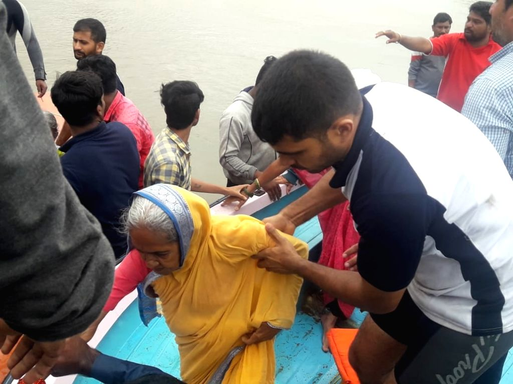Kolhapur: A senior citizen being rescued in Maharashtra's flood affected Kolhapur, on Aug 8, 2019. (Photo: IANS)
