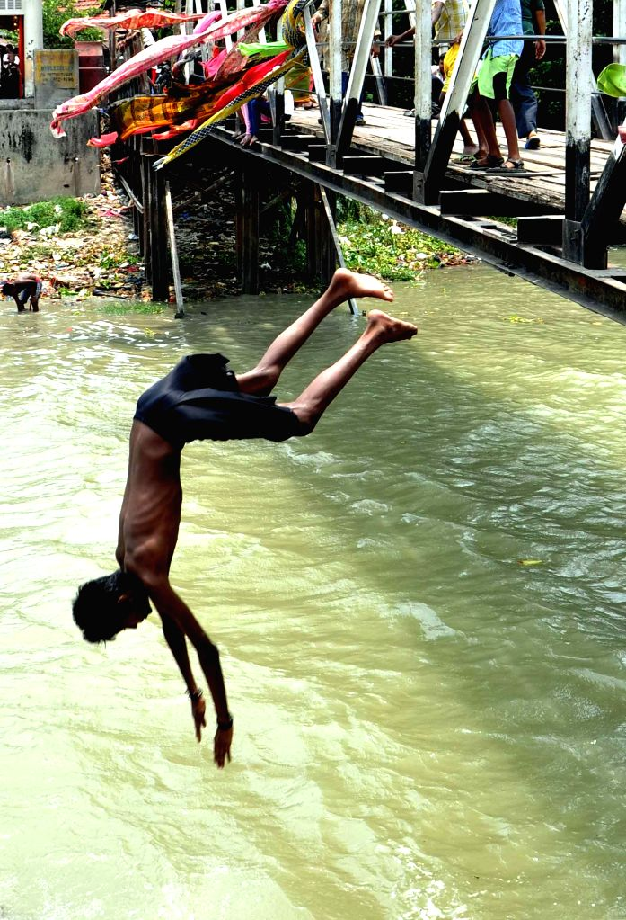 A boy dives into the Hooghly river to beat the heat in Kolkata, on June 12, 2015.