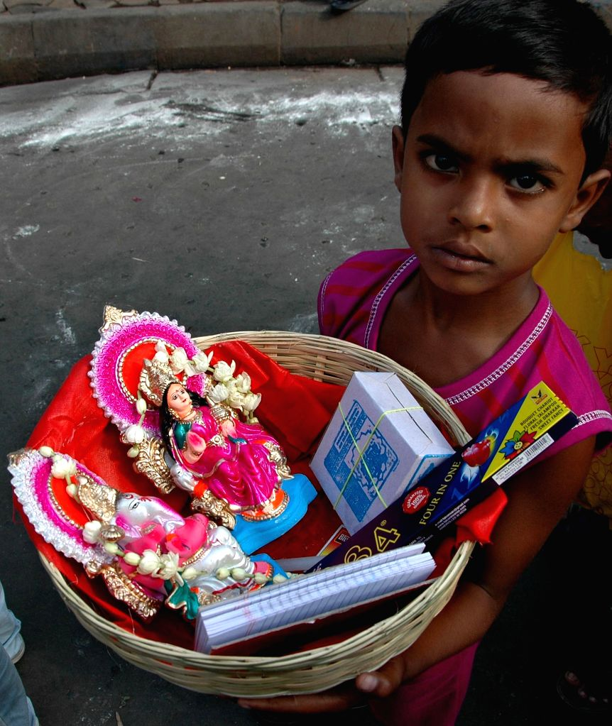 A child holds the idols of lord Ganesha and Lakshmi for worship at a temple on `Poila Baisakh` - Bengali New Year, 1422 - in Kolkata, on April 15, 2015.