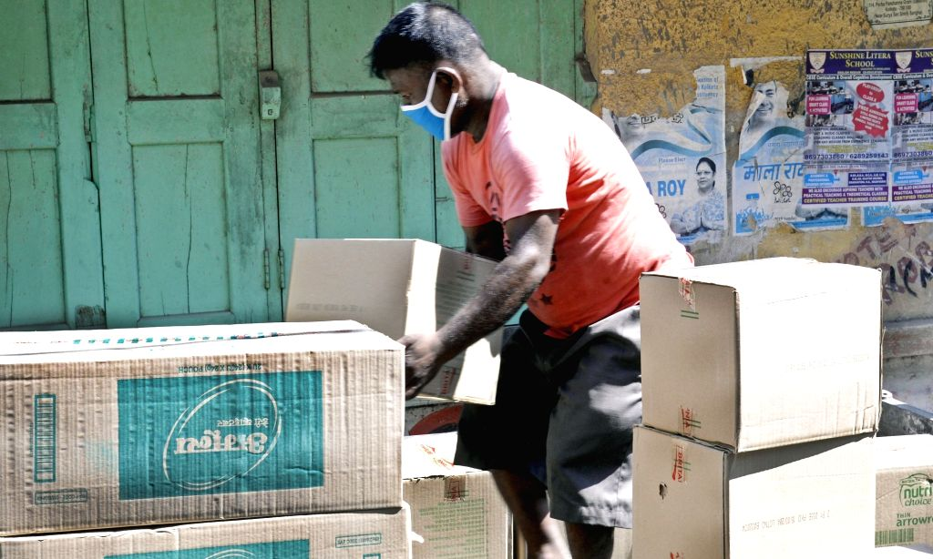 Kolkata: A laborer wearing a mask busy loading cartons of essential commodities on a mini truck on Day 5 of the 21-day countrywide lockdown imposed to contain the spread of novel coronavirus, in Kolkata on March 29, 2020. (Photo: Kuntal Chakrabarty/I