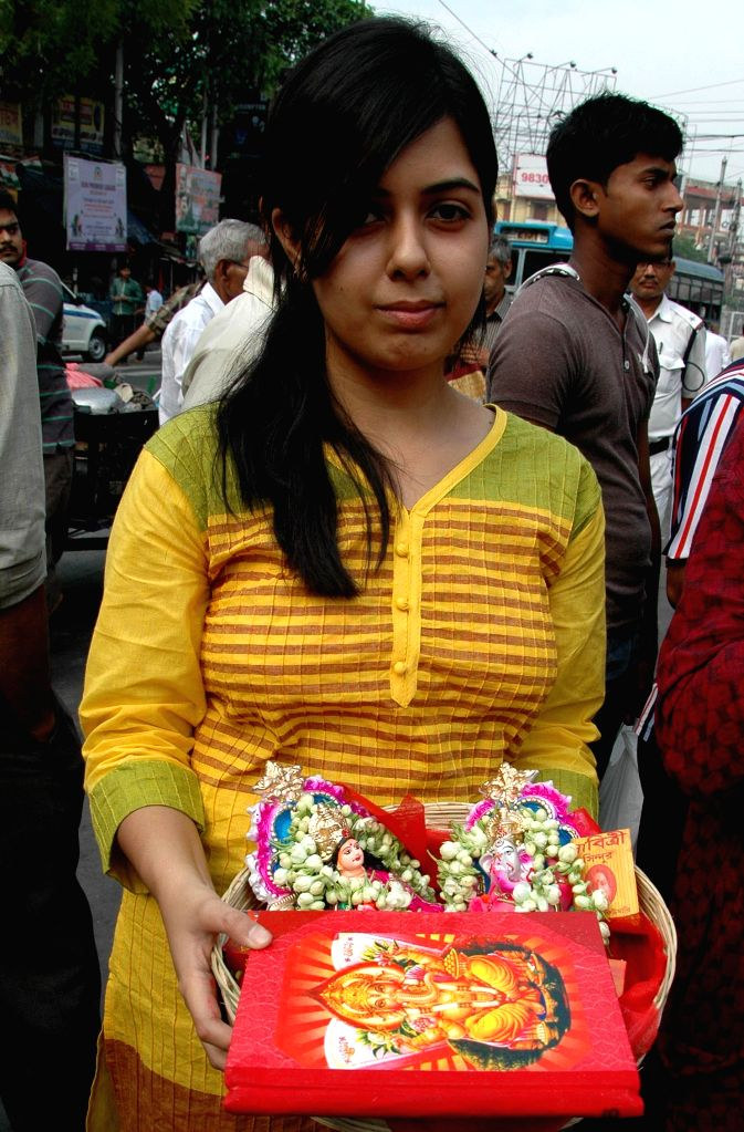A  lady holds the idols of lord Ganesha and Lakshmi for worship at a temple on `Poila Baisakh` - Bengali New Year, 1422 - in Kolkata, on April 15, 2015.