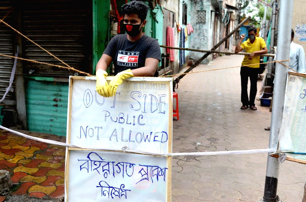 """Kolkata: A locality seals the entrance of its area to rectrict the entry of outsiders by putting up bamboo sticks and banners reading """"Outside Public Not Allowed"""" during the nationwide lockdown imposed to mitigate the spread of COVID-19 pandemic, on"""