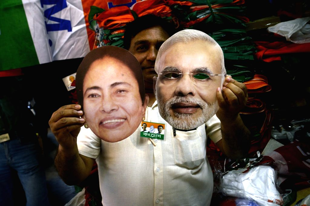 Kolkata: A shopkeeper shows the masks of Prime Minister and BJP leader Narendra Modi and West Bengal Chief Minister and TMC supremo Mamata Banerjee ahead of 2019 Lok Sabha elections, in Kolkata on March 29, 2019. (Photo: Kuntal Chakrabarty/IANS) - Narendra Modi and Mamata Banerjee
