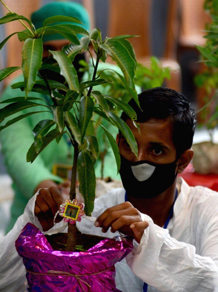 Kolkata : A specially-abled person ties rakhi to a plant on the eve of Raksha Bandhan in Kolkata on Aug 2, 2020.