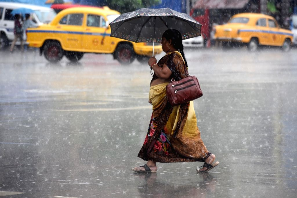 Kolkata: A woman shields herself with an umbrella during rains, in Kolkata on June 29, 2019. (Photo: Kuntal Chakrabarty/IANS)