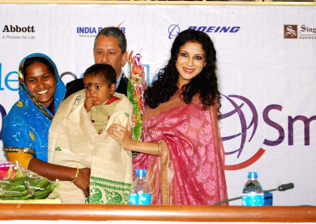Actress Nandana Sen with a child during '5000 Smiles' - a programme organised by India Power Corporation Ltd in Kolkata, on Nov 14, 2014.