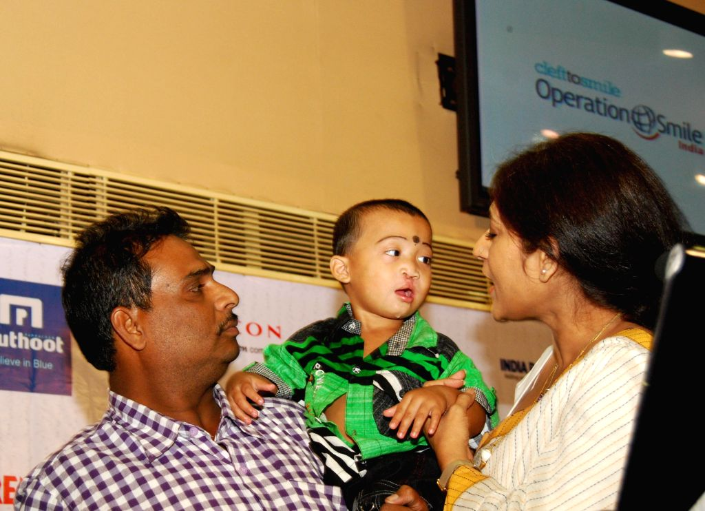 Actress Roopa Ganguly with a child during '5000 Smiles' - a programme organised by India Power Corporation Ltd in Kolkata, on Nov 14, 2014.