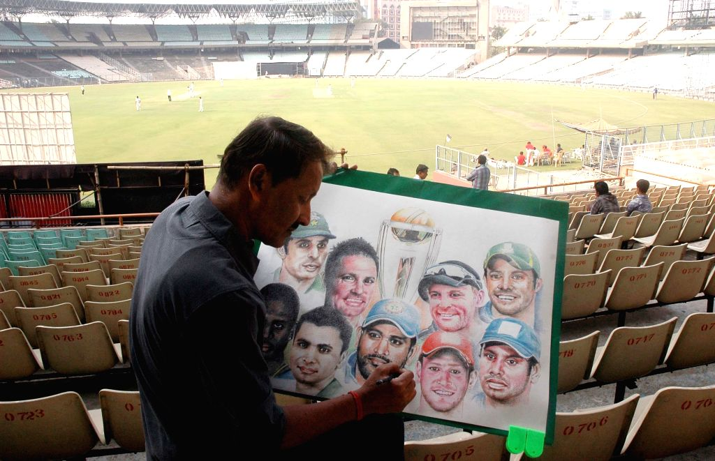 An artist sketches pictures of Indian cricketers with ICC World Cup at the Eden Garden in Kolkata on Feb 13, 2015.