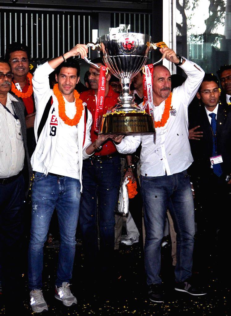 Atletico de Kolkata captain Luis Garcia and coach Lopez Habas arrive at Netaji Subhas Chandra Bose International Airport with the ISL trophy in Kolkata, on Dec 21, 2014. Also seen Atletico .. - Luis Garcia and Sanjiv Goenka