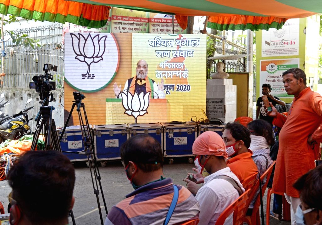 Kolkata: BJP activists watch Union Home Minister Amit Shah addressing 'West Bengal Jan Samvad Rally' via video conferencing, on their mobile phones in Kolkata on June 9, 2020. (Photo: Kuntal Chakrabarty/IANS) - Amit Shah