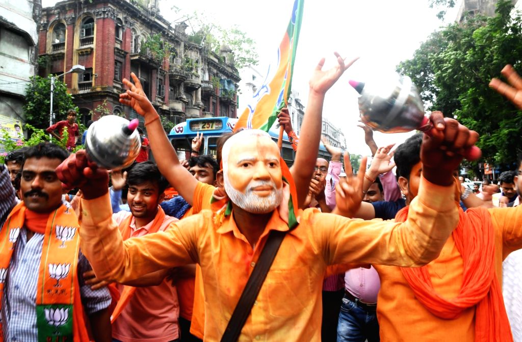 Kolkata: BJP worker wearing Prime Minister Narendra Modi's mask and others celebrate after the party led by Prime Minister Narendra Modi was set to retain power for another five years after making a sweep of the 2019 Lok Sabha battle and mauling the  - Narendra Modi