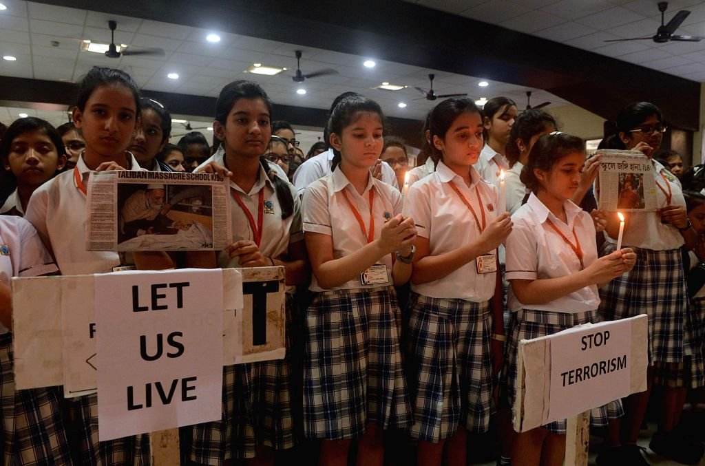 Children participate in a candle light vigil to protest against Tuesday's attack on the Army Public School in Peshawar, Pakistan, that claimed 104 lives mostly those of children, in Kolkata,
