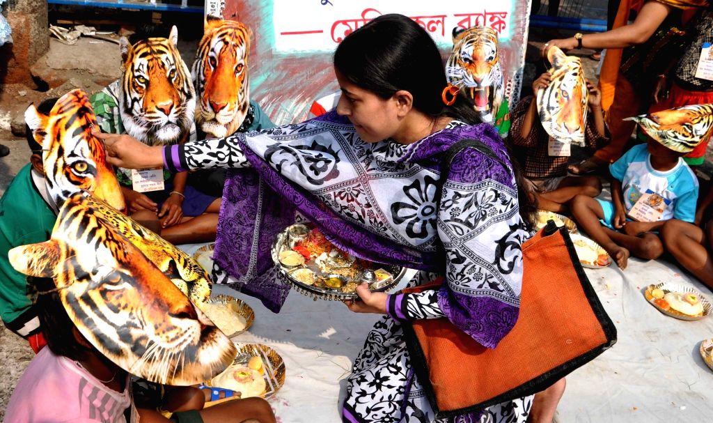 ":Kolkata: Children participate in ""Save Tiger"" campaign during Bhai Duj in Kolkata, on Nov 13, 2015. ."
