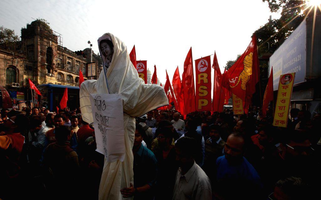 CPI(M) activists hold the West Bengal Chief Minister Mamata Banerjee effigy to protest against Trinamool Congress in Kolkata on Dec 13, 2014. - Mamata Banerjee
