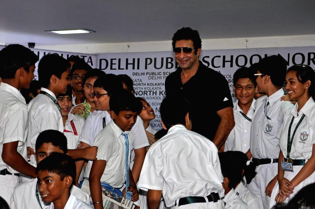 Kolkata: Formar Pakistani cricketer Wasim Akram with school children during a program in Kolkata on May 5, 2015. (Photo: Kuntal Chakrabarty/IANS)