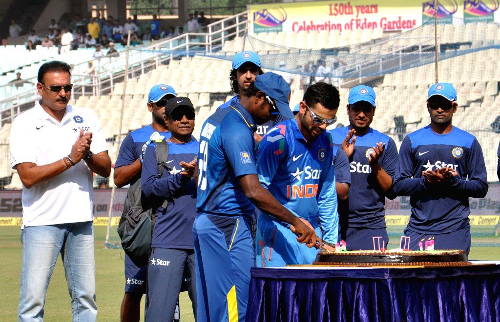 Indian captain Virat Kohli and his Sri Lankan counterpart Angelo Mathews celebrate 150 years of the Eden Gardens in Kolkata, on Nov 13, 2014. Also seen team India director Ravi Shastri. - Virat Kohli