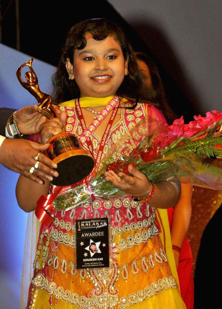 Indian Idol junior Sonakshi Kar receives Best Rising Child Singer award during the 23rd Kalakar Awards in Kolkata on Jan 11, 2014.