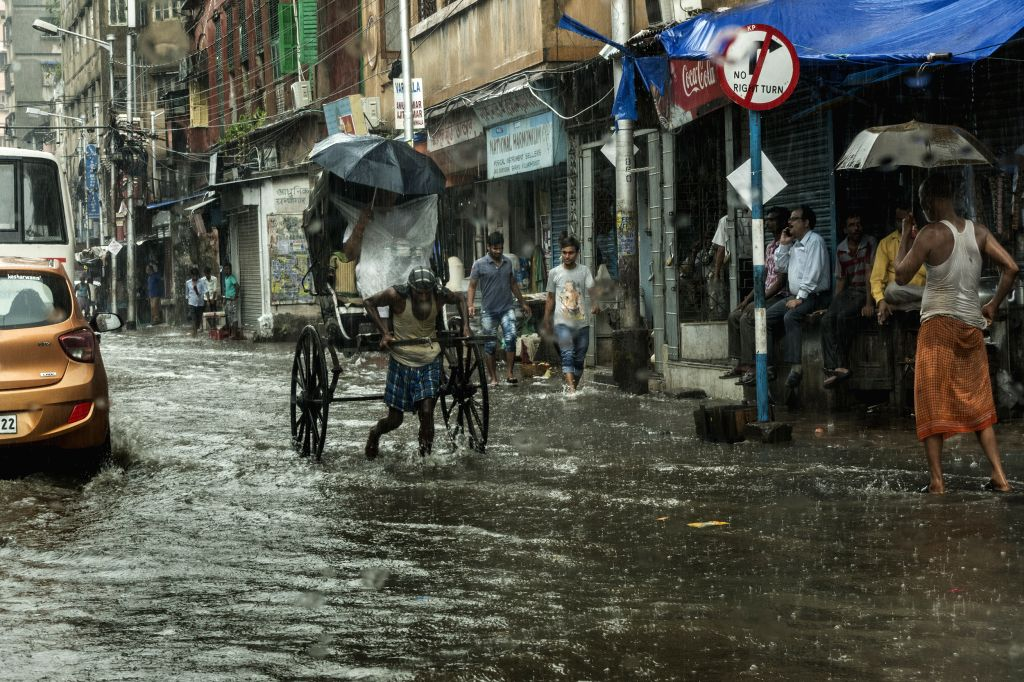 KOLKATA, June 30, 2017 - An Indian hand rickshaw puller carries a passenger during heavy rainfall in Kolkata, capital of eastern Indian state West Bengal, on June 30, 2017.