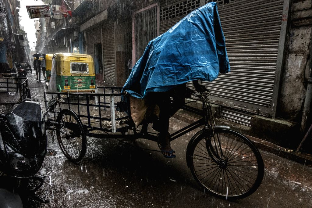 KOLKATA, June 30, 2017 - An Indian labor covers his head with plastic sheet during heavy rainfall in Kolkata, capital of eastern Indian state West Bengal, on June 30, 2017.