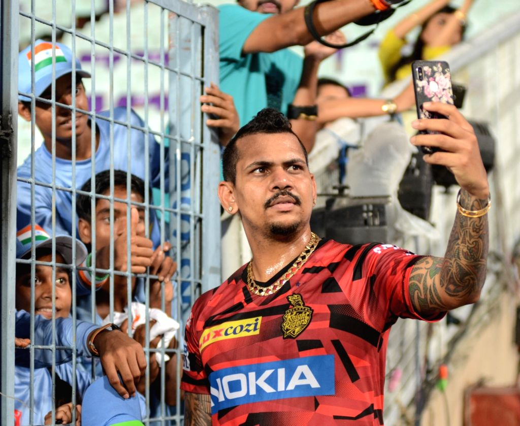 Kolkata Knight Riders' Sunil Narine poses for selfies with fans during a practice session at the Eden Gardens in Kolkata, on April 24, 2019.