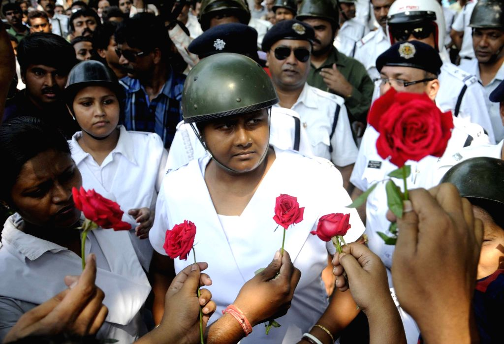 Leftist students present red roses to policemen during a road block staged by them in Kolkata, on April 3, 2015.