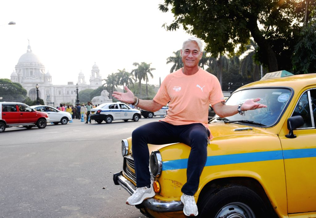 : Kolkata: Legendary American diver Greg Louganis, who is ambassador of  Tata Steel Kolkata 25K sits on the bonnet of a taxi in Kolkata on Dec 13, 2018. (Photo: IANS).