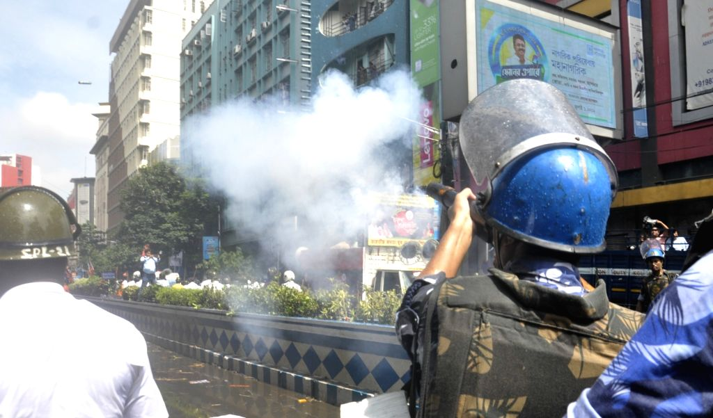 Kolkata: Police fires tear gas shells to disperse BJP Yuva Morcha workers who are protesting against hike in electricity bills in Kolkata on Sep 11, 2019. (Photo: IANS)