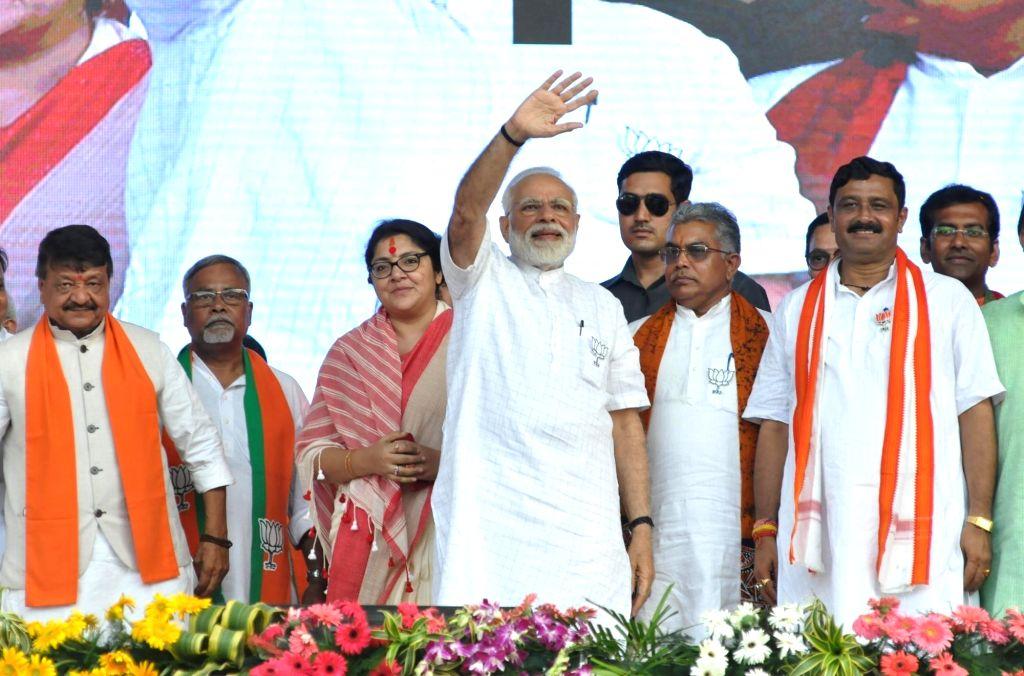 Kolkata: Prime Minister and BJP leader Narendra Modi accompanied by party leaders Kailash Vijayvargiya, Dilip Ghosh, Rahul Sinha and Locket Chatterjee, waves at supporters during a public rally in K0lkata, on April 3, 2019. (Photo: Kuntal Chakrabarty - Narendra Modi, Dilip Ghosh, Rahul Sinha and Chatterjee