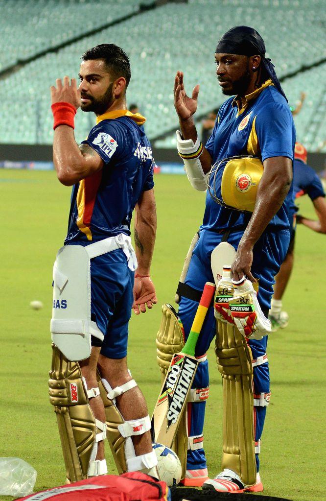 Royal Challengers Bangalore (RCB) captain Virat Kohli with RCB player Chris Gayle during a practice session at the Eden Gardens in Kolkata, on April 10, 2015. - Virat Kohli