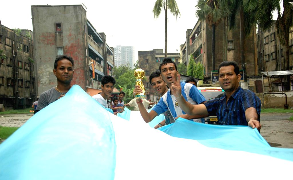 Kolkata`s football fans carry an Argentinian flag along a street in Kolkata on June 21, 2014.