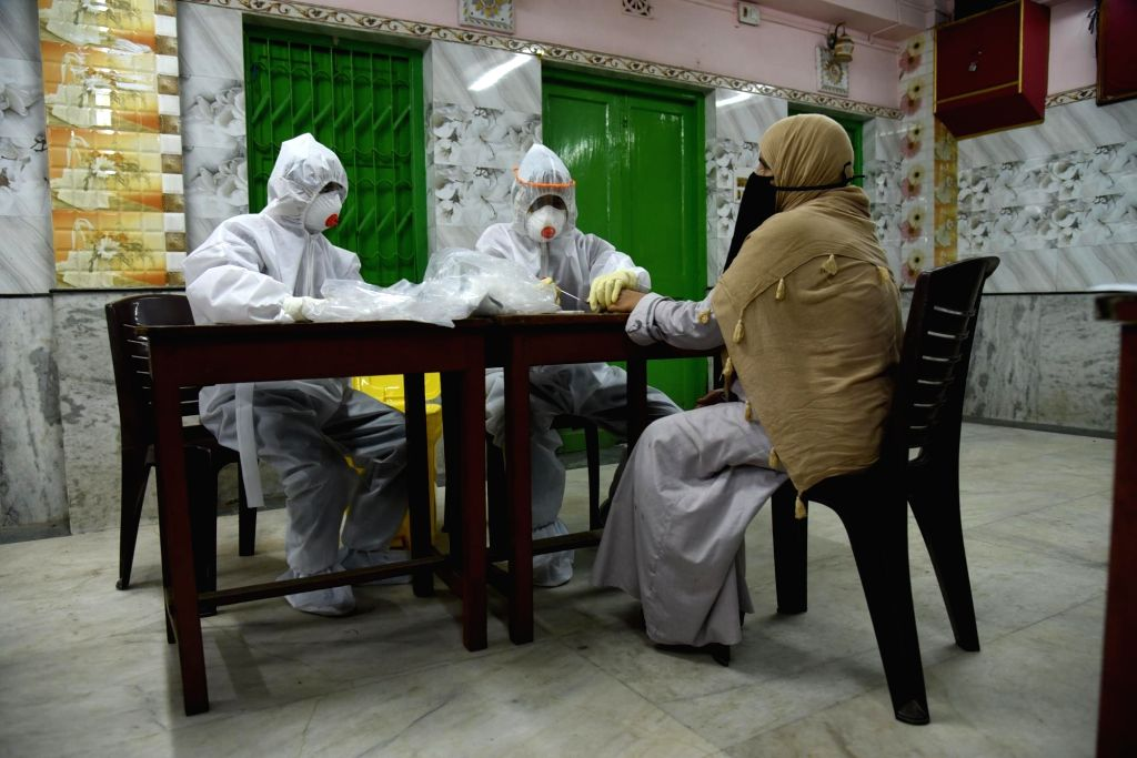 Kolkata: Samples being collected for COVID-19 tests using rapid testing kits by health workers wearing Personal Protective Equipment (PPE) suits at a testing center at Darjipara near Kolkata's Sonagachi during the extended nationwide lockdown imposed