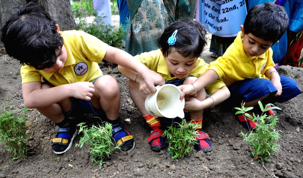 School students plant trees on `World Earth Day` in Kolkata, on April 22, 2015.