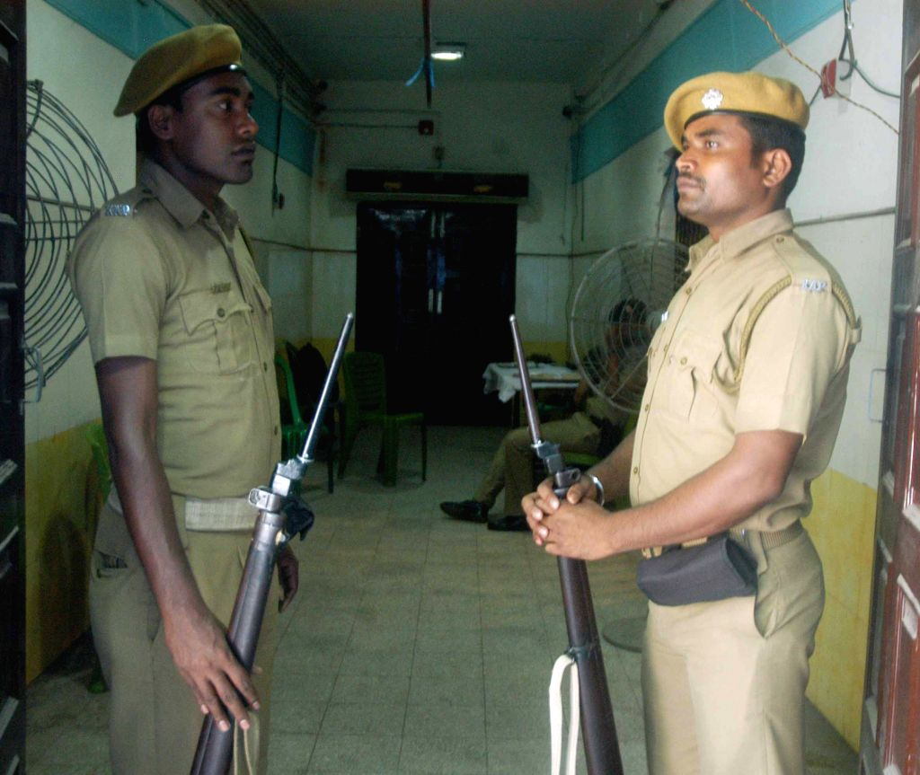 Security personnel stand guard outside a strong room where Electronic Voting Machines (EVM) are kept after KMC polls in Kolkata on April 19, 2015.