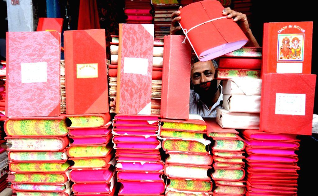 Kolkata : Shop keeper sealing traditional read account books or halkhata ahead of the Begal New Year in Kolkata on April 12, 2021. Pix by Kuntal Chakrabarty.
