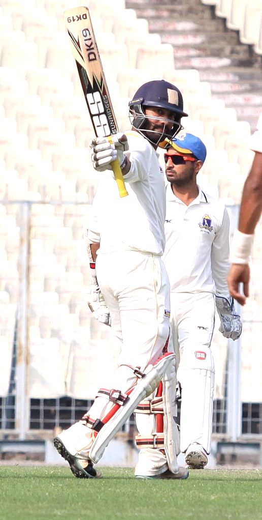 Tamil Nadu player Dinesh Karthik celebrates after scoring a century during a Ranji Trophy match against Bengal at Eden Garden in Kolkata on Jan. 8, 2014.