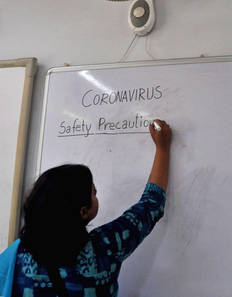 Kolkata: Teacher gives children a class about 'Corona virus' during awareness and safety precaution at a City School in Kolkata on March 11, 2020. (IANS/ Kuntal Chakrabarty)