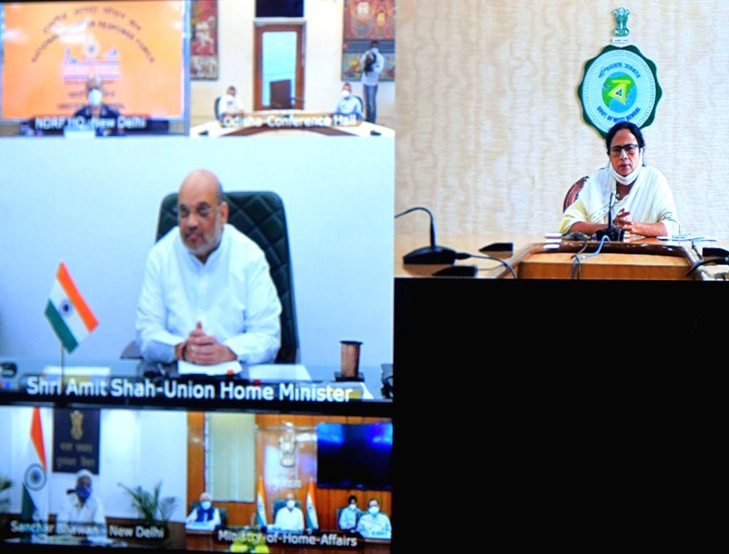 "Kolkata: West Bengal Chief Minister Mamata Banerjee at a video conference with Indian Minister of Home Affairs Amit Shah about super cyclone ""Yash"" at Nabanna at Howrah  in Kolkata   24 May, 2021. (Photo: IANS) - Mamata Banerjee and Affairs Amit Shah"