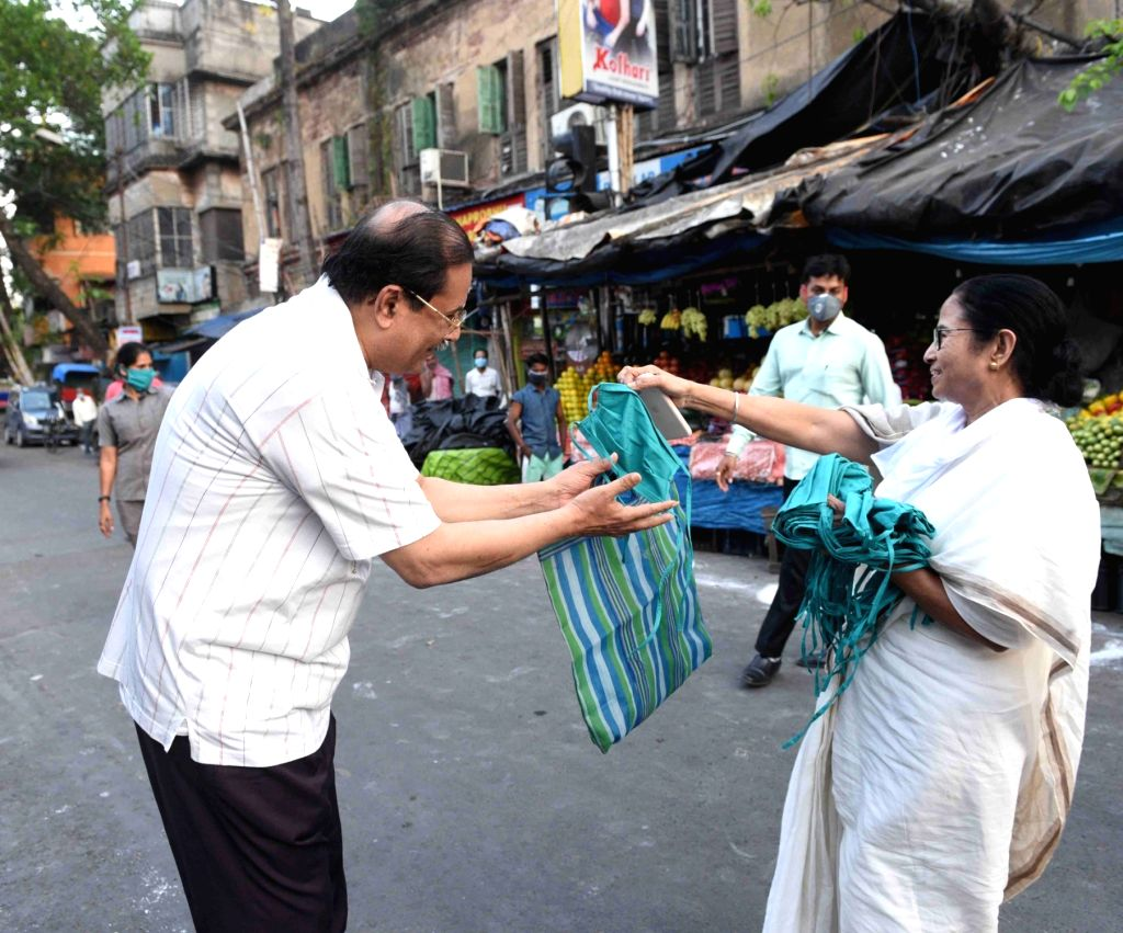 Kolkata: West Bengal Chief Minister Mamata Banerjee distributes masks among people on Day 2 of the 21-day nationwide lockdown imposed by the Narendra Modi government over the coronavirus pandemic; in Kolkata on March 26, 2020. (Photo: IANS) - Mamata Banerjee and Narendra Modi