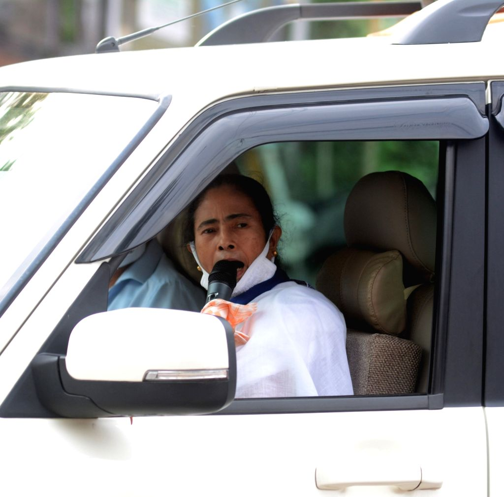 Kolkata: West Bengal Chief Minister Mamata Banerjee interacts with people from a police van during her inspection visit to Kolkata's Raja Bazar during the extended nationwide lockdown imposed to mitigate the spread of coronavirus; on Apr 21, 2020. (P - Mamata Banerjee