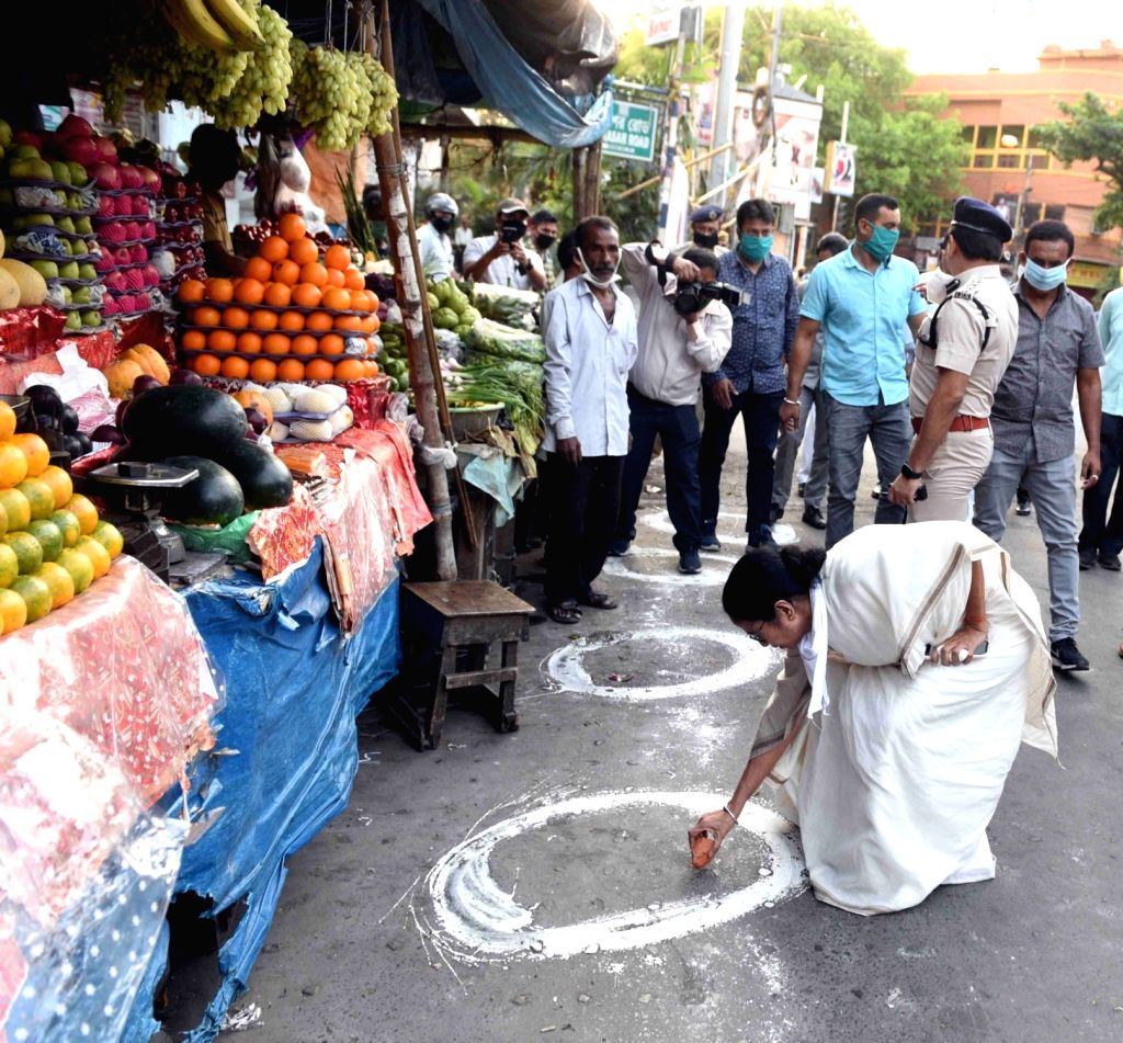 Kolkata: West Bengal Chief Minister Mamata Banerjee marks a street with chalk urging people to stringently follow social distancing on Day 2 of the 21-day nationwide lockdown imposed by the Narendra Modi government over the coronavirus pandemic; in K - Mamata Banerjee and Narendra Modi