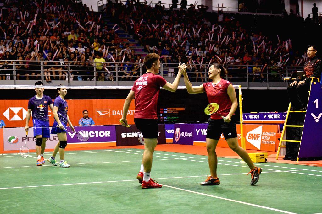 KUALA LUMPUR, Jan. 21, 2018 - Tang Chun Man (L Front) and Tse Ying Suet (R Front) of China's Hong Kong celebrate after the mixed doubles final match against Zheng Siwei and Huang Yaqiong of China at ...