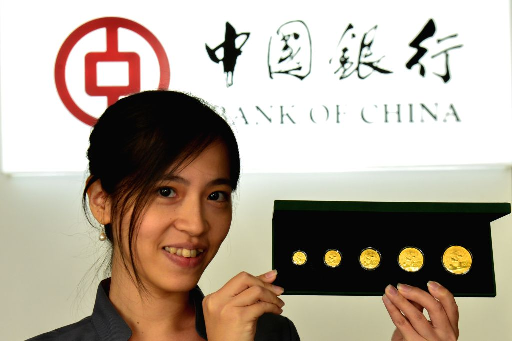 An employee of Bank of China in Malaysia displays the Chinese panda gold coins in Kuala Lumpur, Malaysia, June 17, 2014. Bank of China in Malaysia issued ...