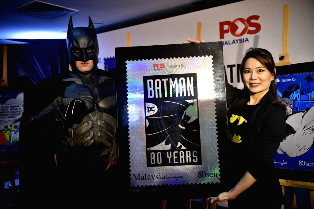 KUALA LUMPUR, Nov. 13, 2019 - A woman and a performer in Batman costumes show the Batman stamp sample during its launching ceremony in Kuala Lumpur, Malaysia, Nov. 13, 2019. Pos Malaysia issued the ...