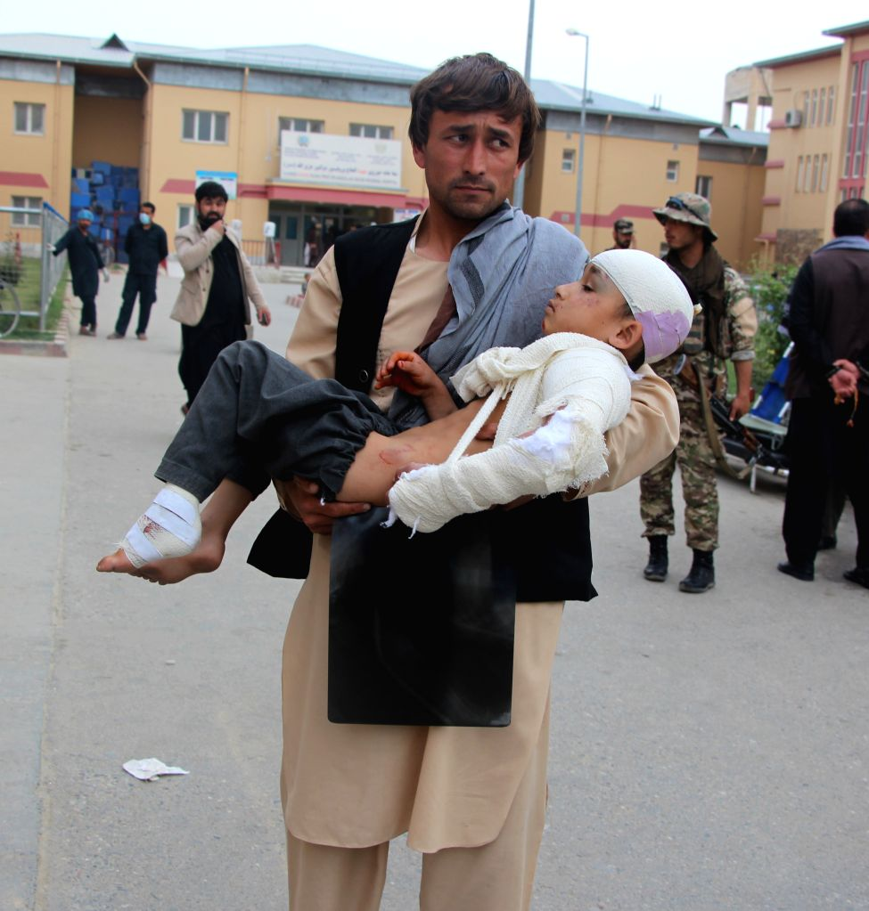KUNDUZ, April. 3, 2018 - An Afghan man carries an injured child after airstrikes in Kunduz province, Afghanistan, April, 3, 2018. Scores of people have been confirmed dead and injured as government ...